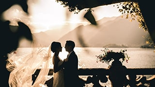 cristiano-ostinelli-sony-alpha-9-bride-and-groom-silhouetted-in-front-of-ocean-under-the-shadow-of-some-trees